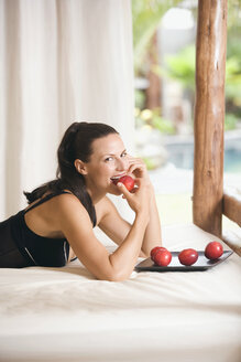 Young woman relaxing on bed, eating plums - ABF00424