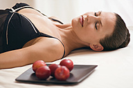 Young woman wearing neglige, relaxing on bed alongside tray with plums - ABF00421
