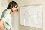 Young man studying construction plan - WESTF09112