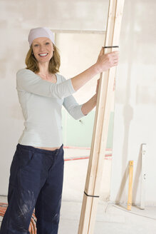 Young woman holding wooden planks, smiling, portrait - WESTF09047
