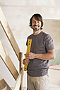 Young man holding spirit level, smiling, portrait - WESTF09021