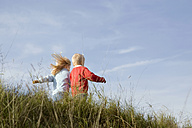 Little girl and boy (3-4) playing  outdoors, rear view - SMOF00174