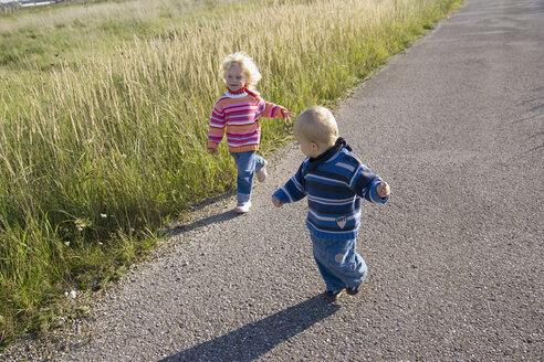 Little girl (2-3) and boy (1-2) running across path - SMOF00149
