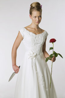 Young bride holding knife and rose, portrait - NHF00909