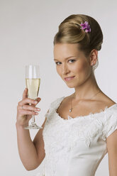 Young bride holding champagne glass, portrait - NHF00897