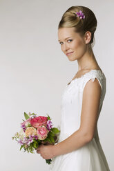 Young bride holding bridal bouquet, side view - NHF00888