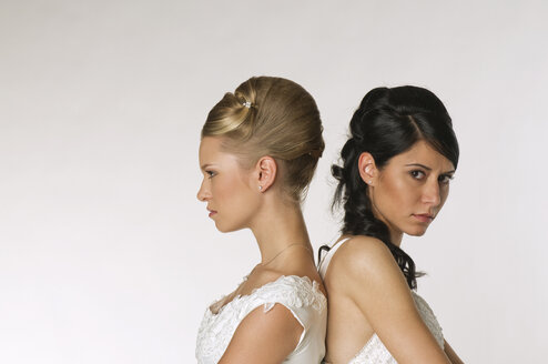 Young brides standing back to back, portrait - NHF00885