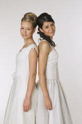 Young brides standing back to back, smiling, portrait - NHF00882