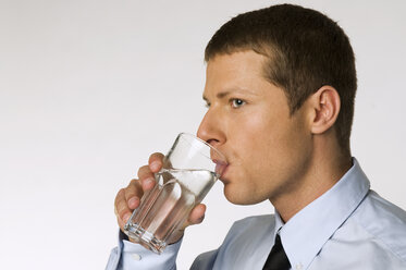 Businessman drinking glass of water - NHF00825