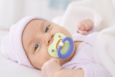 Baby girl (2 months) lying with pacifier, portrait - SMO00288