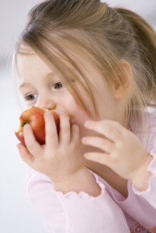 Little girl (3-4) eating an aplle, portrait, close-up - SMO00234