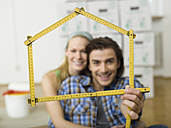 Young couple making house shape with folding rule, portrait - WESTF09796
