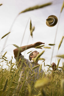 Farmer throwing hat in field - BMF00498
