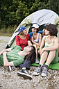 Germany, Friends sitting in front of tent - WESTF09490