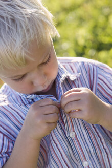 Little boy (2-3) buttoning up his shirt, close up - SMO00276