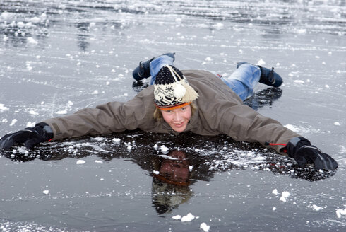 Young male  (16-17) in winter clothes lying on frozen lake, smiling - AWDF00296