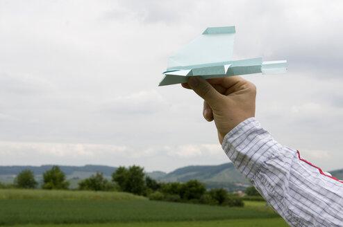 Hand holding paper plane, close-up - AWDF00163
