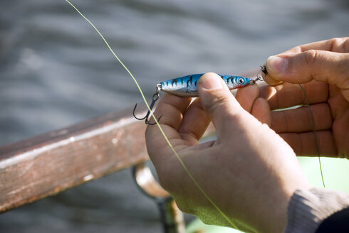 Man's hand  fixing bait on hook, elevated view - AWDF00160