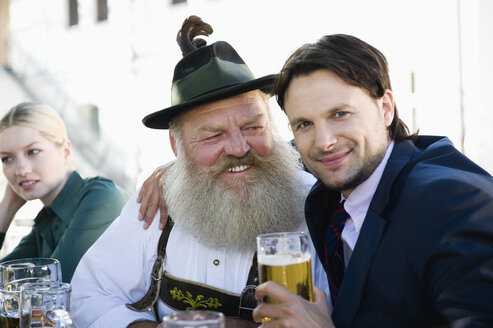Germany, Bavaria, Upper Bavaria, Man in traditional cosume and businessman in beer garden, smiling, portrait - WESTF09723