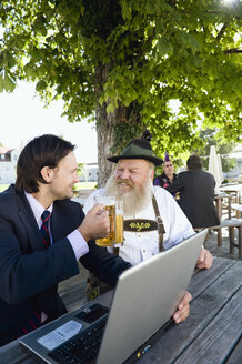 Germany, Bavaria, Upper Bavaria, Senior Bavarian man and young businessman with laptop in beer garden - WESTF09699