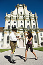 Germany, Bavaria, Upper Bavaria, Asian woman taking picture of Bavarian man with camera phone - WESTF09684