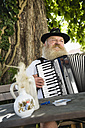 Germany, Bavaria, Upper Bavaria, Senior man in traditional costume playing accordion in beer garden - WESTF09660