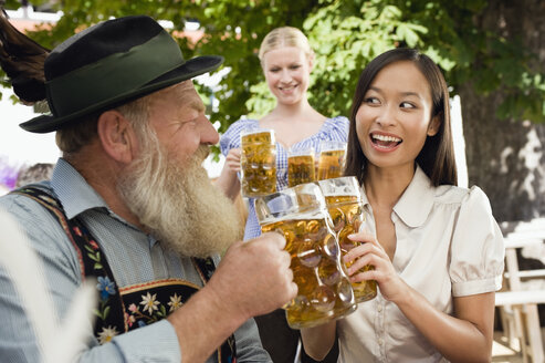 Germany, Bavaria, Upper Bavaria, Bavarian man and Asian woman in beer garden raising stein glasses, portrait - WESTF09639