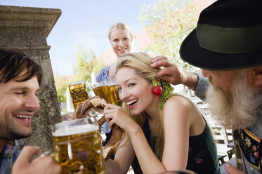 Germany, Bavaria, Upper Bavaria, People in beer garden, waitress in background - WESTF09617