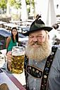 Germany, Bavaria, Upper Bavaria, Senior man in beer garden holding beer stein, portrait - WESTF09608