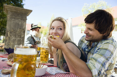 Germany, Bavaria, Upper Bavaria, Young man feeding woman in beer garden - WESTF09605