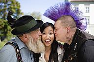 Germany, Bavaria, Upper Bavaria, Two men kissing Asian woman on cheek, portrait - WESTF09551