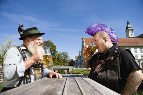 Germany, Bavaria, Upper Bavaria, Man with mohawk hairstyle and Bavarian man in beer garden - WESTF09542