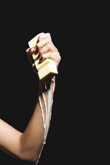Female hand holding melting chocolate bar, close-up - OW00880
