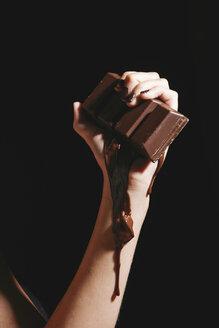 Female hand holding melting chocolate bar, close-up - OW00877
