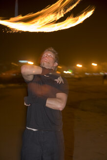 Spain, Canary Islands, Gran Canaria, Young man juggling with torches - PK00300