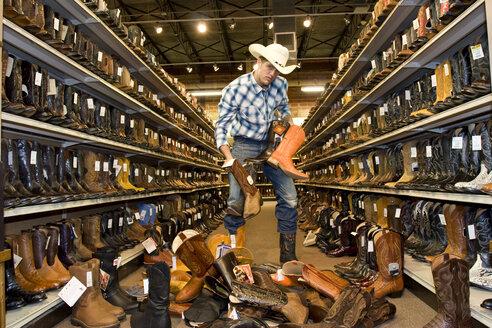 USA, Texas, Dallas, Young man choosing cowboy boots in shoe store - PK00244