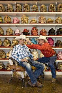 USA, Texas, Dallas, Man trying cowboy hat on - PK00238