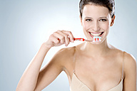 Young woman brushing her teeth, smiling, close up - MAEF01287