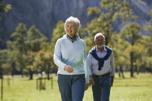 Austria, Karwendel, Senior couple walking across meadow - WESTF10542