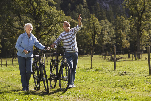 Austria, Karwendel, Senior couple pushing bikes across path - WESTF10533