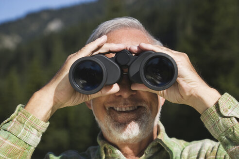 Austria, Karwendel, Senior man looking through binocular, portrait - WESTF10497