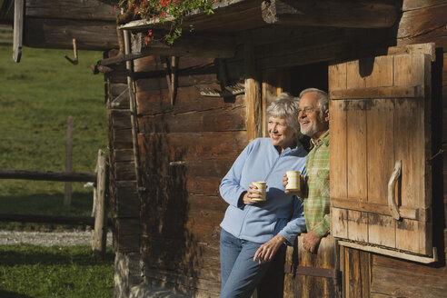 Austria, Karwedel, Senior couple leaning on log cabin, holding mugs - WESTF10467
