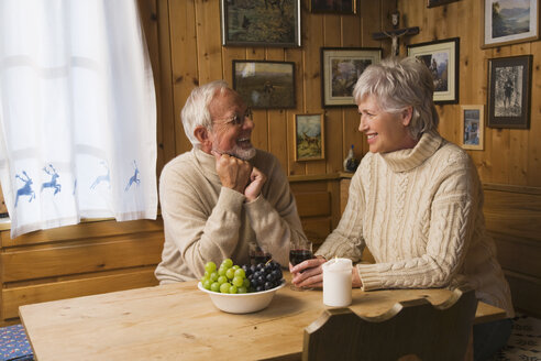 Senior couple sitting at table, smiling - WESTF10416