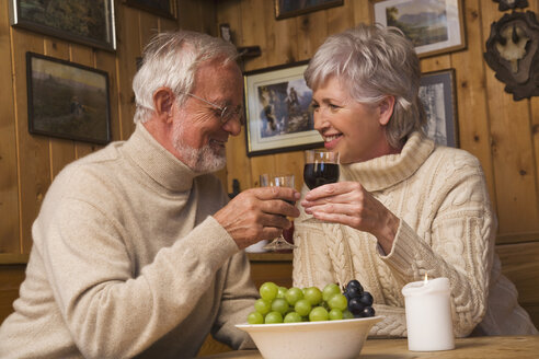 Senior couple toasting with red wine - WESTF10413