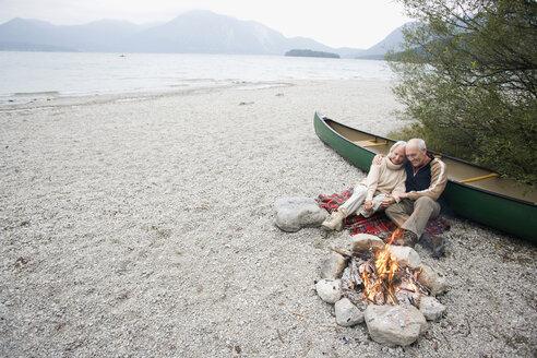 Germany, Bavaria, Senior couple sitting at campfire - WESTF10224