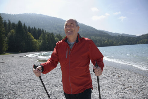 Germany, Bavaria, Walchensee, Senior man with Nordic Walking poles, smiling - WESTF10181