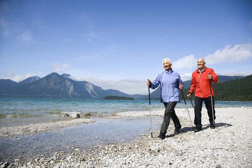 Germany, Bavaria, Walchensee, Senior couple, Nordic Walking on lakeshore - WESTF10178