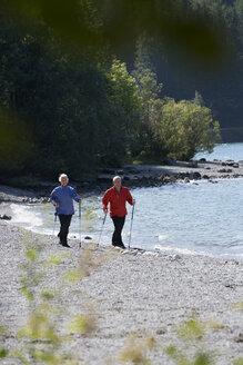 Germany, Bavaria, Walchensee, Senior couple, Nordic Walking on lakeshore - WESTF10175
