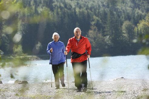 Germany, Bavaria, Walchensee, Senior couple, Nordic Walking on lakeshore - WESTF10172