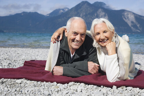 Germany, Bavaria, Walchensee, Senior couple relaxing on lakeshore - WESTF10148